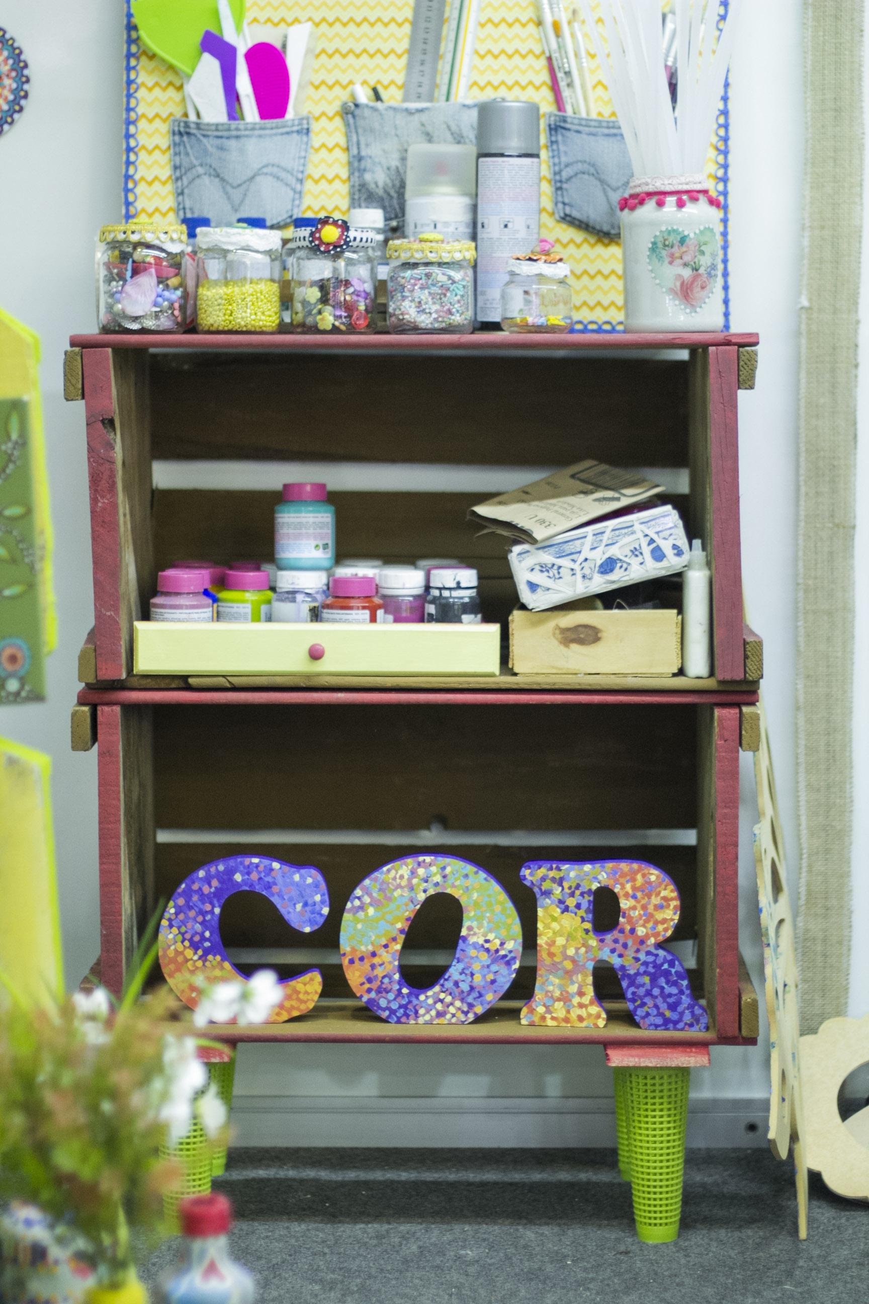 Caixotes viram estante e o trabalho de Jéssica é muito ligado a cores, por isso as letras formando essa palavra