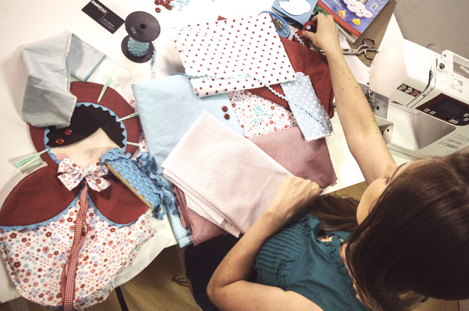 A artesã em meio a tecidos, moldes, agulhas e linhas