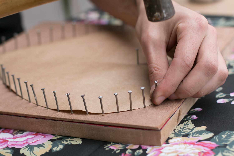 Placa de madeira, com molde de coração e detalhe dos pregos com cerca de 1 cm de distância entre si