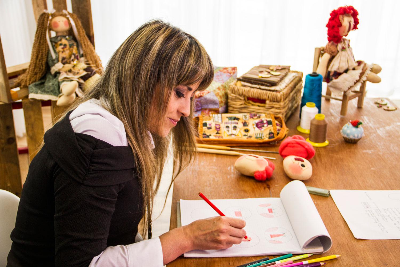 A artesã trabalha em seus desenhos. A partir do papel, as bonecas ganham vida e uma história