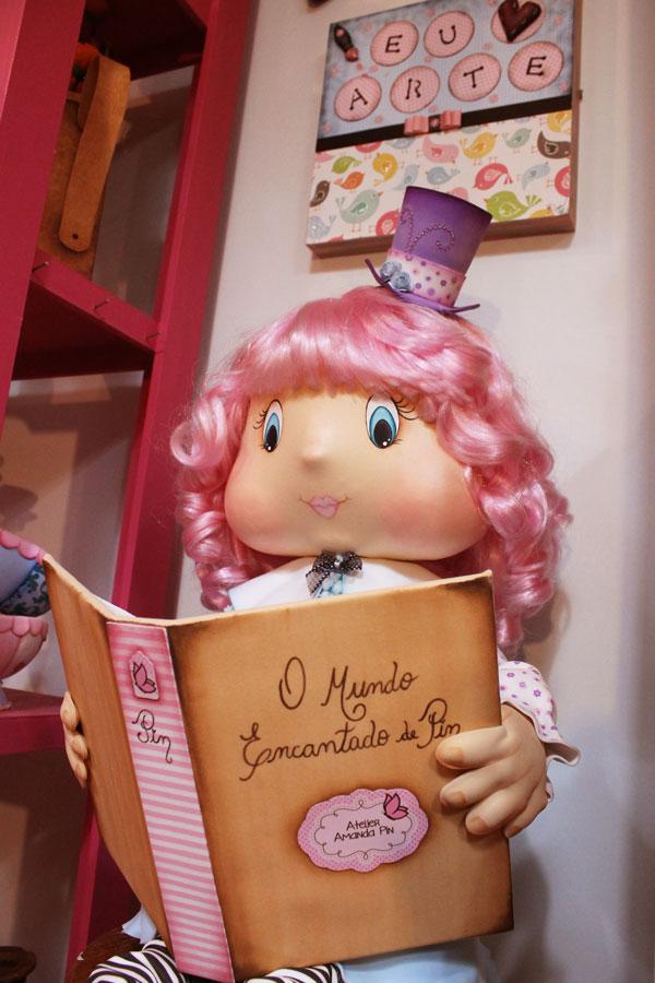 A boneca Amanda Pin lendo o livro do mundo encantado de Pin