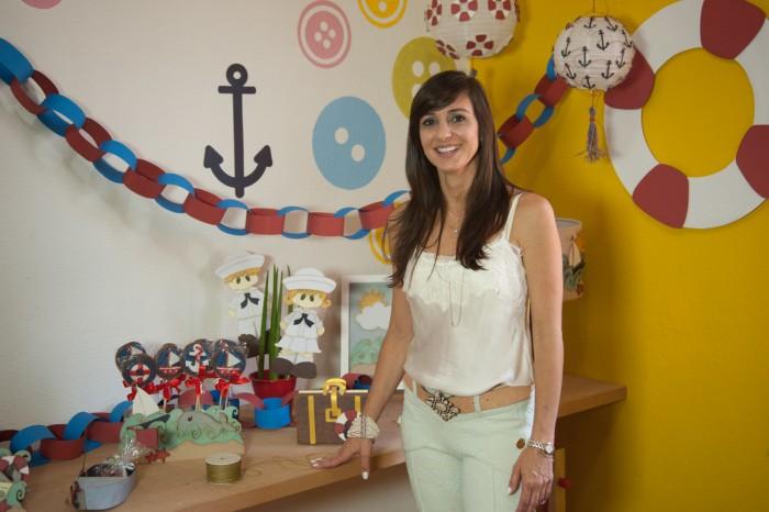 A professora montessoriana e designer do papel Aninha Haddad fala sobre método montessoriano e posa ao lado de uma mesa com decoração navy, com peças desenvolvidas por ela em papel