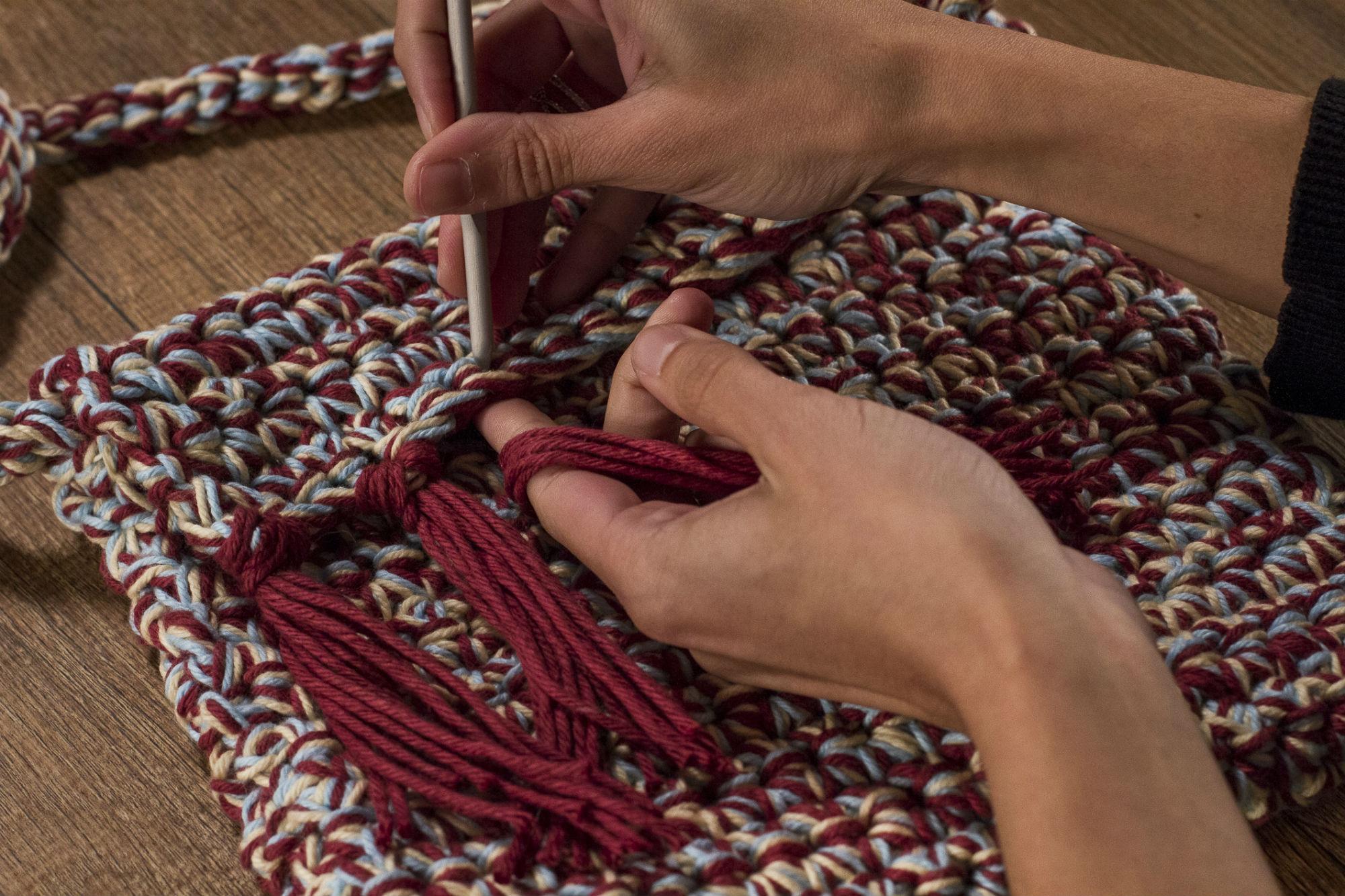 Detalhe charmoso: Marie aplica as franjas na parte superior da bolsa